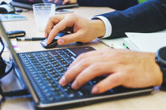 The working atmosphere of a young businessman in a suit is typing on his laptop. Stock Image