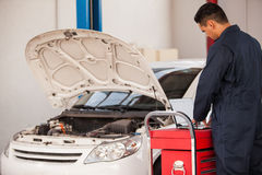 Working at an auto shop with a PC. Young mechanic using a laptop computer and fixing a car at an auto shop Royalty Free Stock Photography