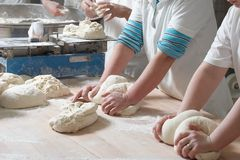 Working bakery team. Women bakery team at work weigh and mixing dough royalty free stock image