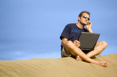 Working on the beach. Surfer working on his laptop in the dunes in Gran Canaria royalty free stock images
