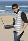 Working at the beach. Young professional male standing with laptop at the beach Stock Image