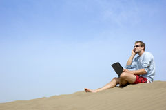 Working on the beach3. Surfer working on his laptop in the dunes in Gran Canaria stock image