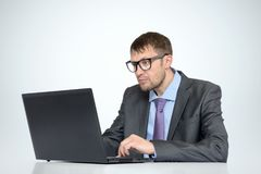 Working bearded man in glasses with a laptop on light background.  Royalty Free Stock Photography