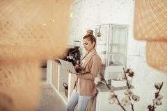 Concentrated woman working at her laptop near coffee table. Always working. Beautiful concentrated woman standing near the coffee table and working at her royalty free stock photos