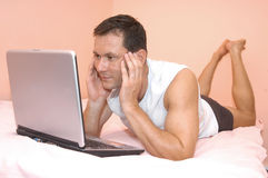 Working in bed. Man using his laptop in bed. He doing work at home stock image