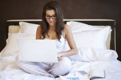 Working in bed Royalty Free Stock Image