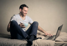 Working in bed Royalty Free Stock Images