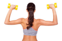 Working those biceps. Shot of a beautiful young woman exercising with dumbbells against white isolated background Stock Photos