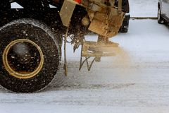 Big red snowplow sands carriageway during snowfall and ice royalty free stock photo