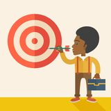 Working black man holding a target arrow. A working black man with strategy on how to get his target market sales higher. Market strategy concept. A Contemporary Stock Image