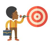 Working black man holding a target arrow. A working black man with strategy on how to get his target market sales higher. Market strategy concept. A Contemporary Stock Photography