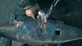 Working blacksmith hits a metal knife with a hammer on anvil. 4K stock footage