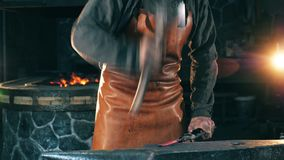 Working blacksmith uses a hammer to hit a knife. Blacksmith forging iron in workshop. Working blacksmith uses a hammer to hit a knife. 4K stock footage