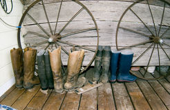 Working Boots. A row of work boots lined up in front of decorative wagon wheels, ready and waiting for use on the ranch Royalty Free Stock Image