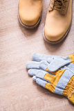 Working boots and protective gloves on wooden Stock Photography