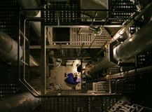 Working at the bottom of a LNG tanker. A worker is working in a LNG tanker during maintenance. Leveling the zero poin Stock Photography