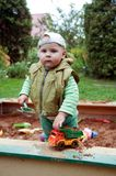 Working boy playing in a sandbox. With a car Stock Images