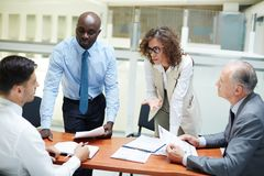 Working briefing. Group of colleagues brainstorming while having discussion of new strategies royalty free stock photo