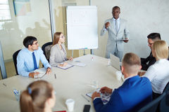 Working briefing. Serious managers listening to confident businessman explanations royalty free stock photography