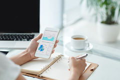 Working with business chart. Business woman making notes when analyzing diagram on her phone Royalty Free Stock Photography