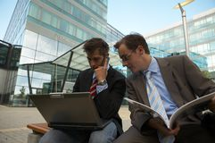 Working business men. Two business men sitting and working on a laptop Royalty Free Stock Photos
