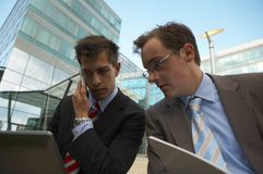 Working business men. Two business men are sitting outside and working on a laptop Royalty Free Stock Image