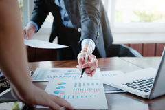 Working business people analyse high performance marketing data. Royalty Free Stock Photography