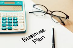 Working on business plan and calculating cost with pen and eye glasses. Closeup the word business plan on white paper. Concept of Starting A Business and Stock Photo