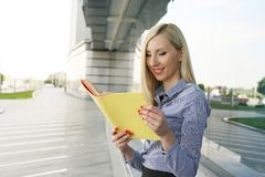 Working business woman reading document. Working woman reading something in notebook. Business woman reading document Stock Photo