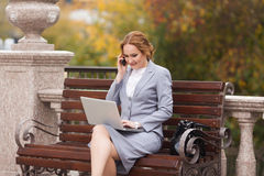 Working business women with laptop. Working business woman with laptop sitting on the bench Stock Image