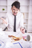 Working. Businessman angry over spilled coffee on documents Royalty Free Stock Photo