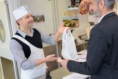 Working in butchers shop - shop assistant and client Royalty Free Stock Photos