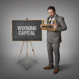 Working capital text on blackboard with businessman Royalty Free Stock Photo