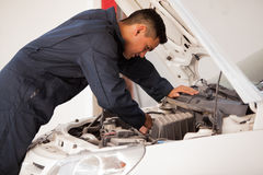 Working on a car engine. Young mechanic working on a car engine at an auto shop Stock Photography