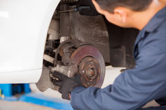 Working on a car suspension. Young mechanic working on a car and fixing its suspension at an auto shop Royalty Free Stock Photo
