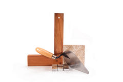 Working with ceramic tiles. Tile, trowel, wooden triangle on a white background Stock Image