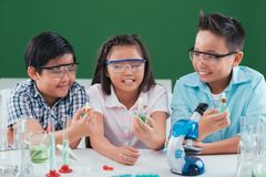 Working in chemistry class. Vietnamese preteen students in goggles working in chemistry class Stock Photography