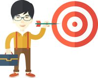Working chinese man holding a target arrow. A working chinese man with strategy on how to get his target market sales higher. Market strategy concept. A Stock Photography