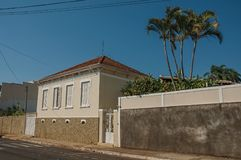 Working-class old house with wall and palm tree in an empty street on a sunny day at San Manuel. stock photos