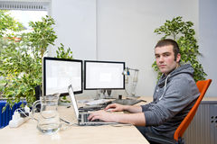 Working in the Cloud. Concept, with a young employee, using various electronic devices online, collaborating internationally through the cloud. The ideal of a royalty free stock photography