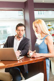 Working colleagues - a man and a woman - in cafe Stock Images