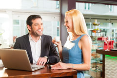 Working colleagues - a man and a woman - in cafe Stock Image