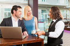 Working colleagues - a man and a woman - in cafe Stock Photos