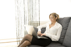 Working with comfort. Woman working on her laptop at home Royalty Free Stock Image