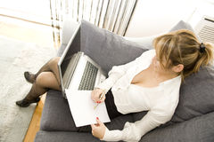 Working with comfort. Woman working on her laptop at home Royalty Free Stock Images