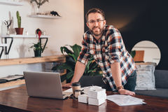 Working from the comfort of home. Portrait of a smiling young entrepreneur leaning on a table at home in front of a laptop and boxes ready for delivery to Royalty Free Stock Photo