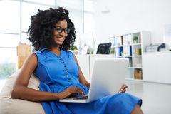Working with comfort. Smiling African-American woman sitting in bean bag chair and working on laptop Stock Image