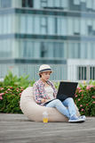 Working in comfort. Young woman sitting in bean bag and working on laptop Royalty Free Stock Photos