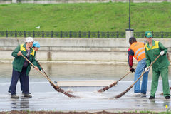 Working Company Zelenstroy sweep puddle together with the promenade of the Gulf. City Cheboksary, Stock Photography