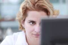 Working on a computer. Close up of the eye of a female researcher in front of a computer monitor in a laboratory Stock Image